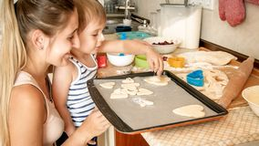 Closeup portrait of young mother with toddler boy holding baking pan and making cookies on kitchen. Closeup portrait of mother with toddler boy holding baking stock image