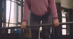 Closeup portrait of young motivated athletic muslim female in hijab lifting weights in gym indoors.  stock footage