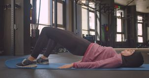 Closeup portrait of young motivated athletic muslim female in hijab making pelvis lifting in gym indoors.  stock footage