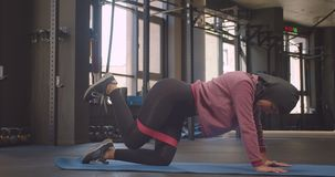 Closeup portrait of young motivated athletic muslim female in hijab making resistance training lifting leg indoors.  stock video footage