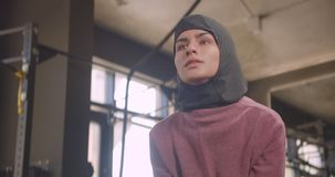 Closeup portrait of young motivated athletic muslim female in hijab making squats with dumbbell in gym indoors.  stock footage