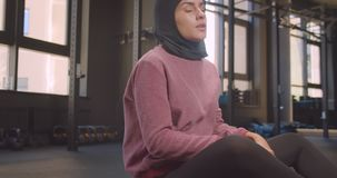 Closeup portrait of young motivated athletic muslim female in hijab working out with ball in gym indoors.  stock video