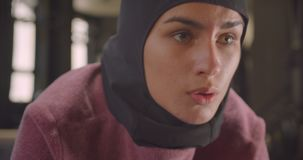 Closeup portrait of young motivated athletic muslim female in hijab working out in gym indoors