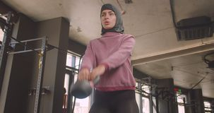 Closeup portrait of young motivated athletic muslim female making squats with dumbbell in gym indoors.  stock video footage