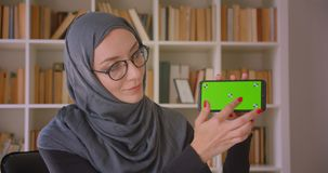 Closeup portrait of young muslim businesswoman in hijab using phone and showing green chroma key screen to camera in. Library indoors stock video footage
