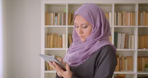 Closeup portrait of young muslim female in hijab using the tablet and looking at camera standing in library indoors.  stock footage