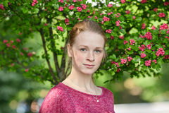 Closeup portrait of young natural beautiful redhead woman in fuchsia blouse posing against blossoming tree with blurred green foli Stock Photo