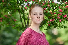 Closeup portrait of young natural beautiful redhead woman in fuchsia blouse posing against blossoming tree with blurred green foli Stock Image