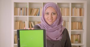 Closeup portrait of young pretty arabian female in hijab using the tablet and showing green chroma screen to camera in. Library indoors stock video