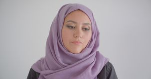 Closeup portrait of young pretty arabian woman in hijab looking at camera with background isolated in white.  stock video footage