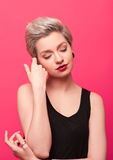 Closeup portrait of young pretty blond woman on pink background Stock Photo