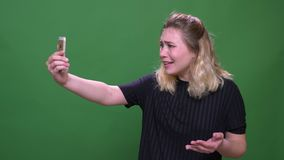 Closeup portrait of young pretty blonde caucasian female having a video call on the phone with background isolated on stock video