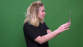 Closeup portrait of young pretty blonde caucasian female having a video call on the tablet with background isolated on stock video