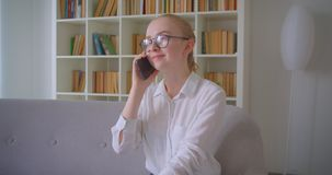 Closeup portrait of young pretty caucasian blonde female student in glasses having a phone call smiling cheerfully. Sitting on the couch indoors in the stock video
