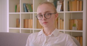Closeup portrait of young pretty caucasian blonde female student in glasses looking at camera sitting on the couch. Indoors in the apartment stock video footage