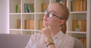 Closeup portrait of young pretty caucasian blonde female student in glasses posing in front of the camera sitting on the. Couch indoors in the apartment stock footage