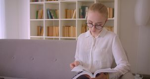 Closeup portrait of young pretty caucasian blonde female student in glasses reading a book and looking at camera sitting. On the couch indoors in the apartment stock video