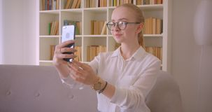 Closeup portrait of young pretty caucasian blonde female student in glasses taking selfies on the phone smiling. Cheerfully sitting on the couch indoors in the stock footage