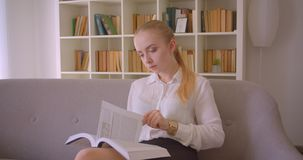 Closeup portrait of young pretty caucasian blonde female student reading a book and looking at camera sitting on the. Couch indoors in the apartment stock video