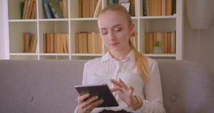 Closeup portrait of young pretty caucasian blonde female student using the tablet looking at camera smiling happily. Sitting on the couch indoors in the stock footage