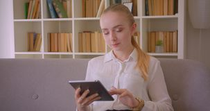 Closeup portrait of young pretty caucasian blonde female student using the tablet looking at camera smiling sitting on. The couch indoors in the apartment stock video