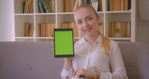 Closeup portrait of young pretty caucasian blonde female student using the tablet and showing green chroma screen to. Camera sitting on the couch indoors stock footage