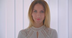 Closeup portrait of young pretty caucasian businesswoman smiling cheerfully turning to camera indoors in a white room.  stock video