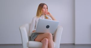 Closeup portrait of young pretty caucasian businesswoman using the laptop being thoughtful looking to the side sitting. In armchair indoors in a white room stock video