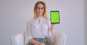 Closeup portrait of young pretty caucasian businesswoman using the tablet and showing green screen to camera sitting in. The armchair in a white room stock video