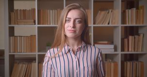 Closeup portrait of young pretty caucasian female student being confused looking at camera in the college library stock footage