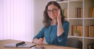 Closeup portrait of young pretty caucasian female student in glasses studying with the tablet looking at camera smiling stock video
