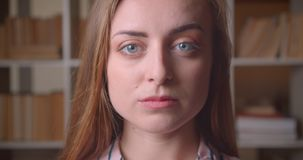 Closeup portrait of young pretty caucasian female student looking at camera in the college library indoors.  stock video