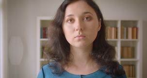 Closeup portrait of young pretty caucasian female student looking at camera in the college library indoors stock footage