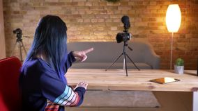 Closeup portrait of young pretty caucasian female video blogger turning to camera and saluting streaming live indoors in. Apartment stock footage