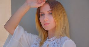 Closeup portrait of young pretty caucasian female with yellow dyed hair posing in front of the camera.  stock footage