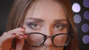 Closeup portrait of young pretty caucasian girl fixing her glasses looking at camera and smiling with bokeh background.  stock video footage