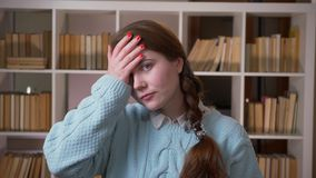 Closeup portrait of young pretty female student making a face palm being annoyed looking at camera in the university. Library indoors stock video