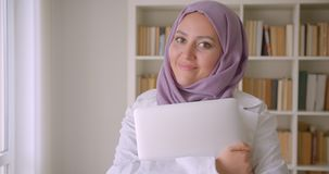 Closeup portrait of young pretty muslim female doctor in hijab holding a laptop looking at camera smiling happily in. Library stock footage