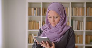 Closeup portrait of young pretty muslim female in hijab using the tablet and looking at camera standing in library.  stock footage