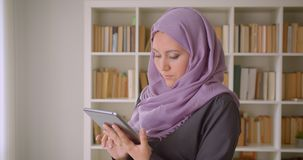 Closeup portrait of young pretty muslim female in hijab using the tablet and looking at camera standing in library. Indoors stock footage