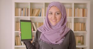 Closeup portrait of young pretty muslim female in hijab using the tablet and showing green chroma screen to camera in. Library indoors stock video
