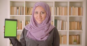Closeup portrait of young pretty muslim female in hijab using the tablet and showing green chroma screen to camera in. Library stock footage