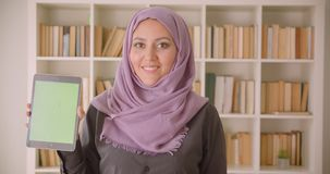 Closeup portrait of young pretty muslim female in hijab using the tablet and showing green screen to camera in library.  stock video