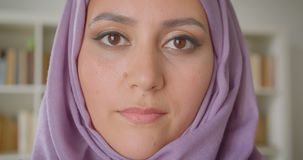 Closeup portrait of young pretty muslim female student in hijab looking at camera smiling cheerfully in library indoors. With bookshelves on the background stock video footage
