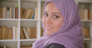Closeup portrait of young pretty muslim female student in hijab turning and looking at camera smiling happily in library. With bookshelves on the background stock video footage