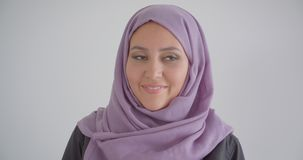 Closeup portrait of young pretty muslim woman in hijab looking at camera smiling happily with background isolated in. White stock video footage