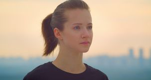 Closeup portrait of young pretty sporty female jogger in a black t shirt looking at the beautiful sunset outdoors stock video footage
