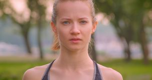 Closeup portrait of young pretty sporty female jogger looking at camera in the park in urban city outdoors.  stock footage