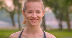 Closeup portrait of young pretty sporty female jogger looking at camera smiling happily in the park in urban city. Outdoors stock footage