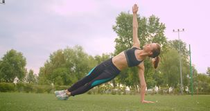 Closeup portrait of young pretty sporty fitness girl doing side plank exercise stretching her arm in the park in urban. City outdoors stock footage